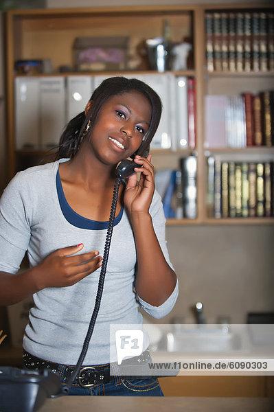 USA  Texas  Junge Frau am Telefon im Büro  lächelnd