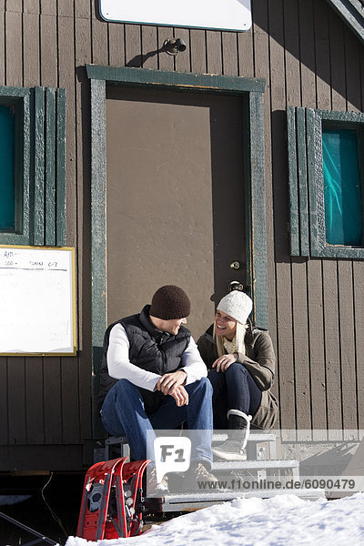 A man and woman sit together on door steps with snowshoes and enjoy the day.