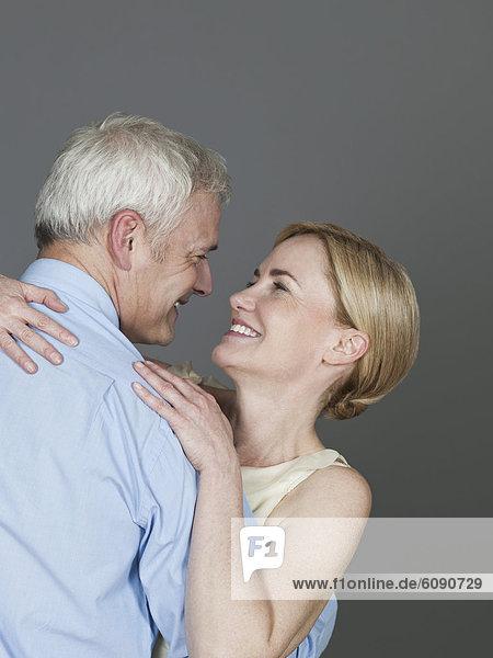 Ein reifes Paar  das sich umarmt und lächelt.