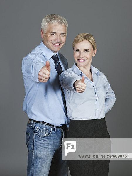 Erwachsenes Paar zeigt Daumen hoch  lächelnd  Portrait
