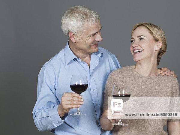 Erwachsenes Paar mit Wein  lächelnd