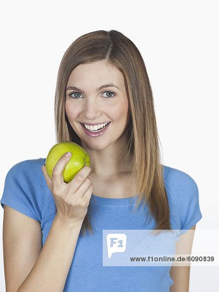 Junge Frau hält Apfel  lächelnd  Portrait