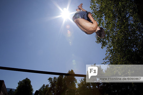 A professional slackliner plays around on the slackline on a university campus in Missoula  Montana.
