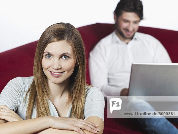 Frau lächelt  Mann benutzt Laptop im Hintergrund