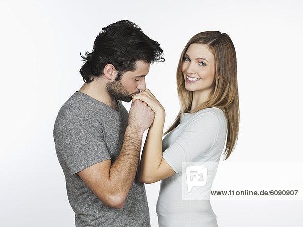 Mann küsst Frauenhand  lächelnd