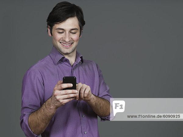 Junger Mann mit Handy  lächelnd