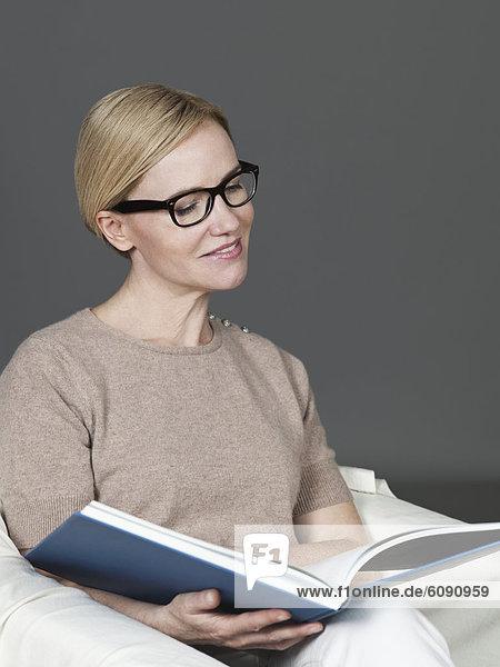 Reife Frau liest Buch  lächelnd