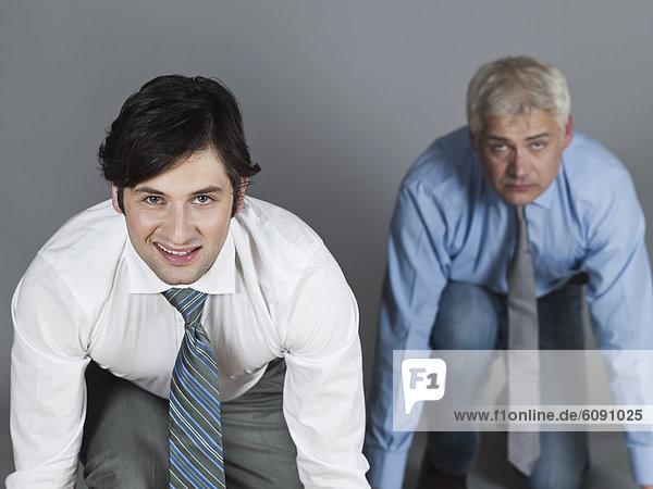 Konkurrierende Geschäftsleute in Startposition lächelnd  Portrait