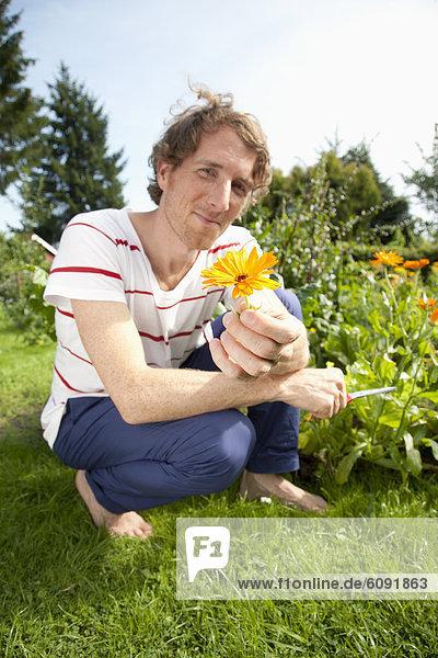 Mann mit Ringelblume im Kleingarten