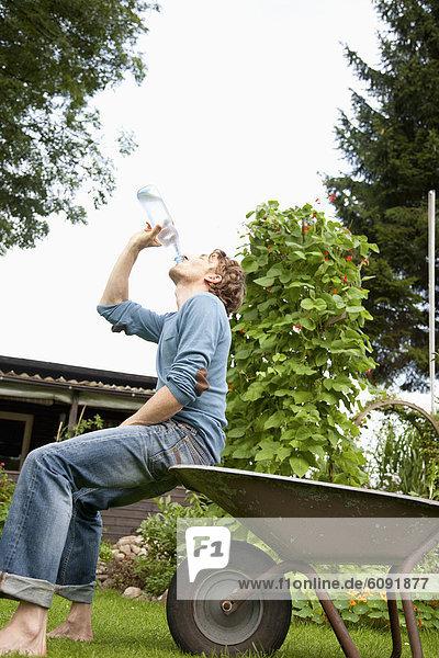 Mann sitzt auf Schubkarre und Trinkwasser im Schrebergarten