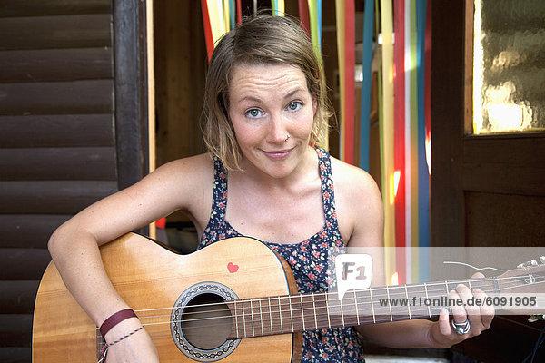 Frau zupft Gitarre im Schrebergarten