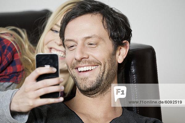 Paar beobachtet Handy  lächelnd  Nahaufnahme