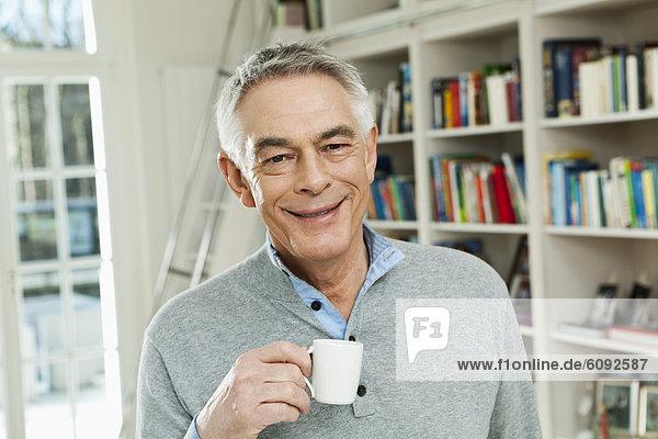 Senior mit Kaffeetasse  lächelnd  Portrait