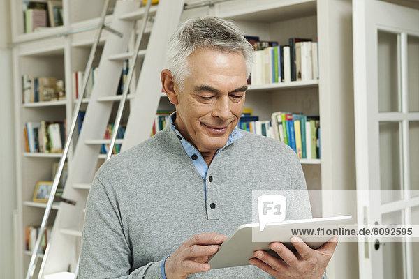 Senior Mann mit Tablet PC  lächelnd.