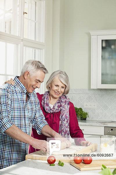 Mann und Frau bei der Zubereitung des Essens  lächelnd