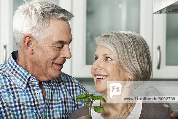 Deutschland  Berlin  Seniorenpaar schaut sich an  lächelnd