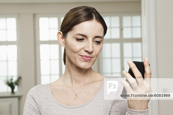 Reife Frau beim Anblick des Handys