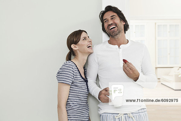 Erwachsenes Paar lächelnd  Mann mit Erdbeere