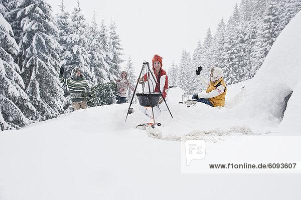 Österreich  Salzburg  Mann und Frau am Kamin  Menschen mit Weihnachtsbaum im Hintergrund