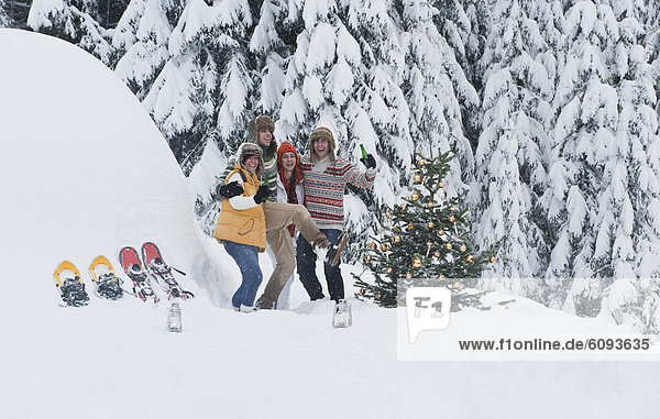 Österreich  Salzburg  Männer und Frauen beim Tanzen am Weihnachtsbaum im Winter