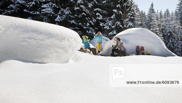 Österreich  Salzburger Land  Familie beim Iglu sitzend