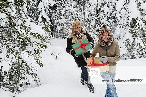 Österreich  Salzburger Land  Paar mit Weihnachtsgeschenk und Wandern im Schnee