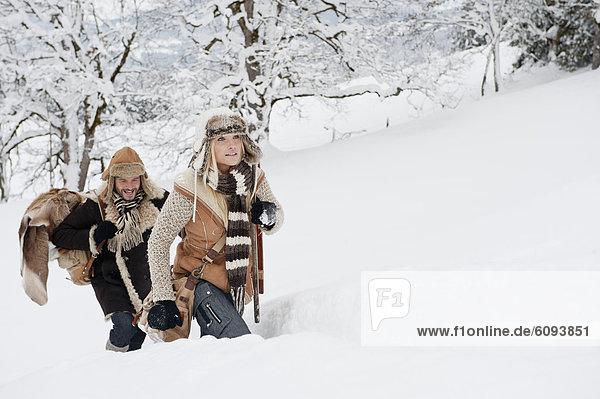 Österreich  Salzburger Land  Paar Wanderungen durch die Winterlandschaft  lächelnd
