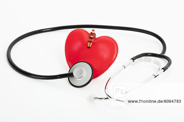 Figurine sitting on heart with stethoscope on white background