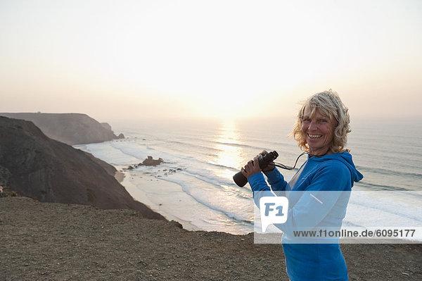 Portugal  Algarve  Sagres  Seniorin mit Fernglas am Strand
