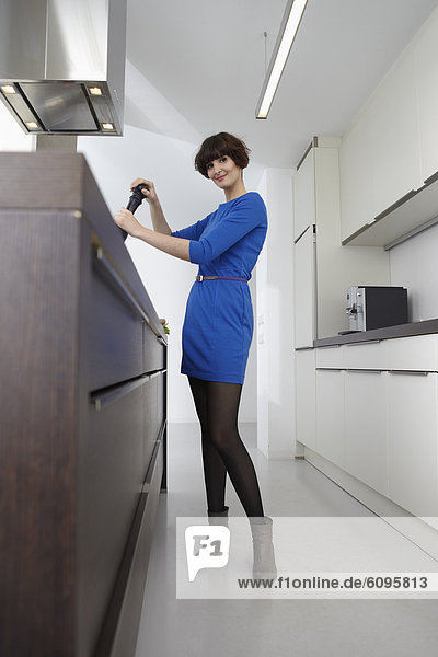 Young woman with pepper mill in kitchen  smiling  portrait