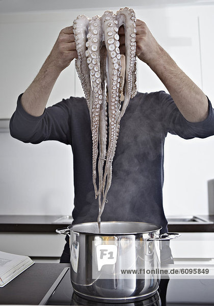 Mittlerer Erwachsener Mann kocht Tintenfisch in der Küche Mittlerer Erwachsener Mann kocht Tintenfisch in der Küche