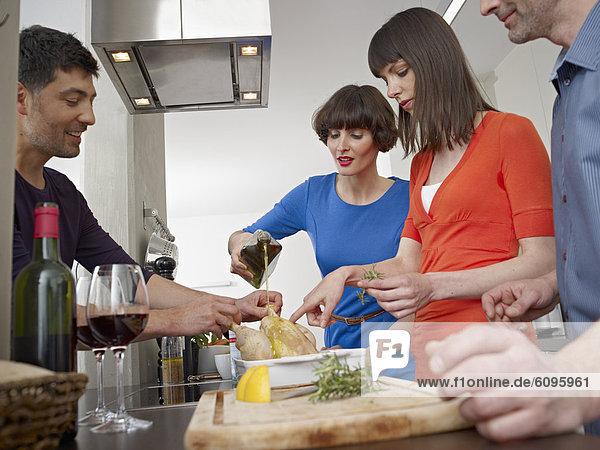 Männer und Frauen kochen gemeinsam in der Küche