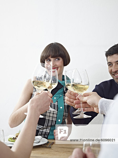 Men and women clinking glasses