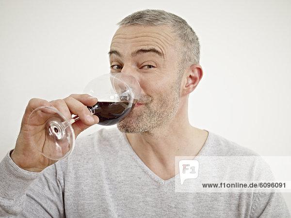 Reifer Mann trinkt Wein in der Küche  Porträt