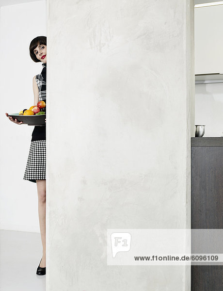 Young woman with plate behind wall