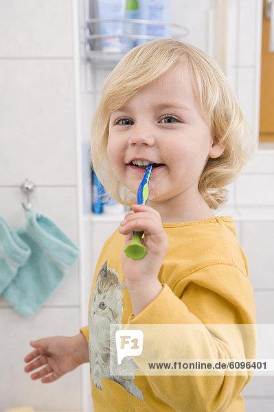Girl brushing her teeth in bathroom  close up