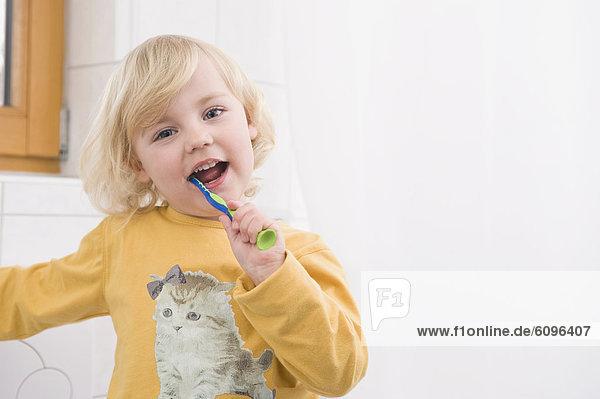 Girl brushing her teeth in bathroom  close up  portrait