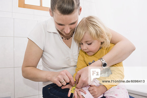 Mother sticking bandage on daughter hand