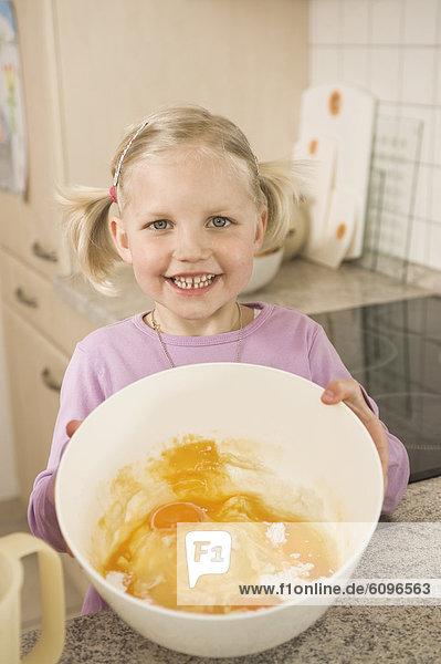 Mädchen hält Schale mit Eigelb und Mehl  lächelnd  Portrait
