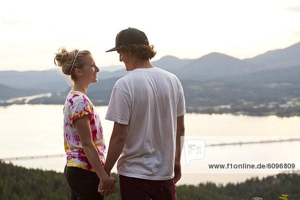 halten  lächeln  junger Erwachsener  junge Erwachsene  Sonnenuntergang  See  Ignoranz  jung  groß  großes  großer  große  großen  Erwachsener