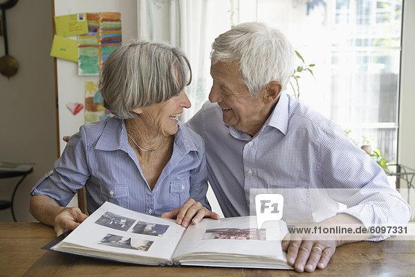 Germany  Bavaria  Senior couple with photo album  smiling