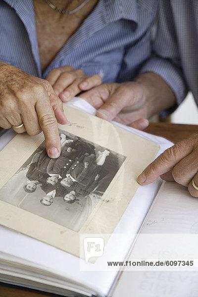 Germany  Bavaria  Senior couple with photo album