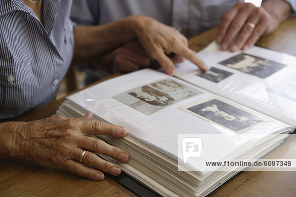 Germany  Bavaria  Senior couple with photo album