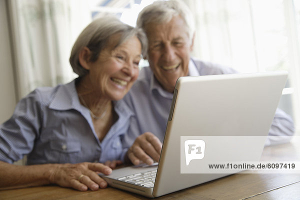 Germany  Bavaria  Senior couple using laptop at home  smiling