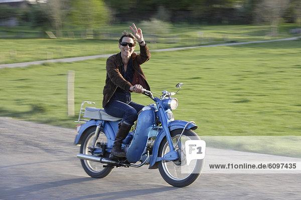 Reife Frau auf altem Moped der 1960er Jahre  lächelnd