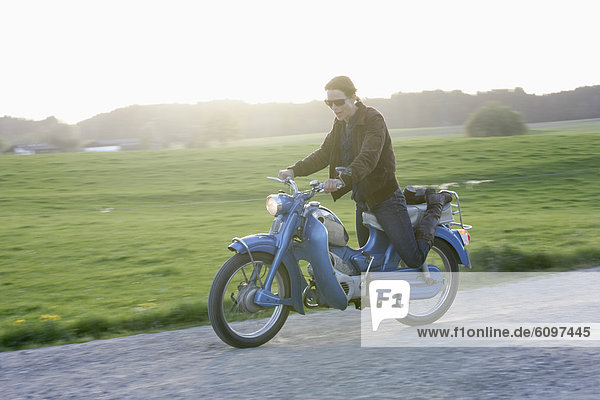 Mature woman riding old moped of 1960s