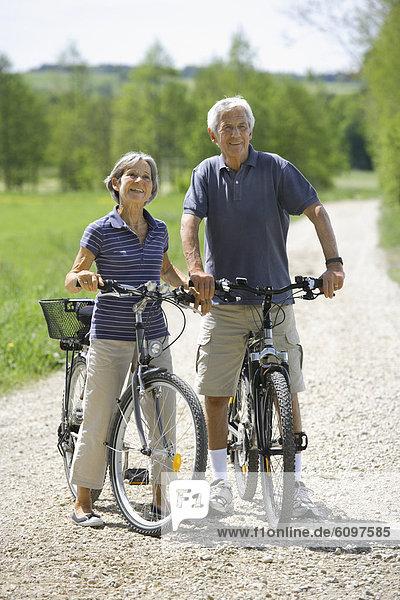 Germany  Bavaria  Senior couple with bicycle  smiling