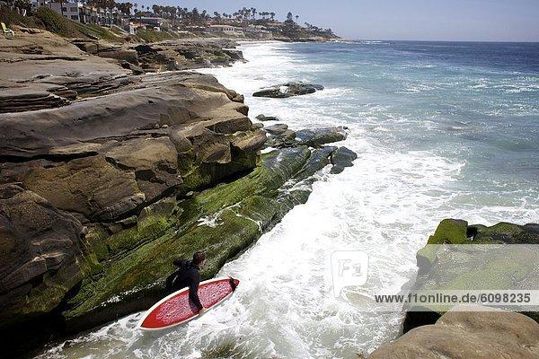 zwischen  inmitten  mitten  Felsbrocken  Wasser  Strand  springen  gehen  Wellenreiten  surfen