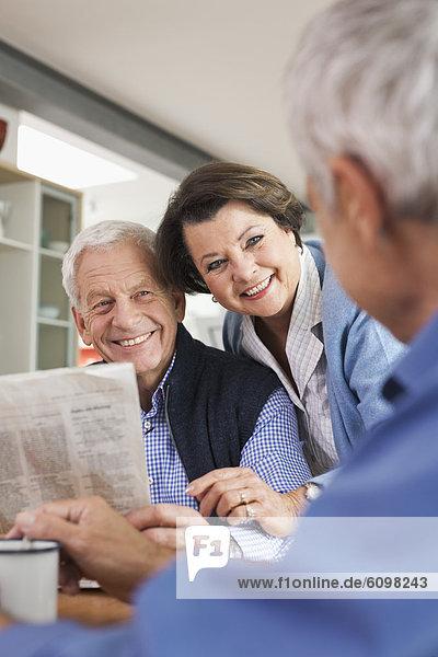 Senior man reading newspaper  man and woman smiling