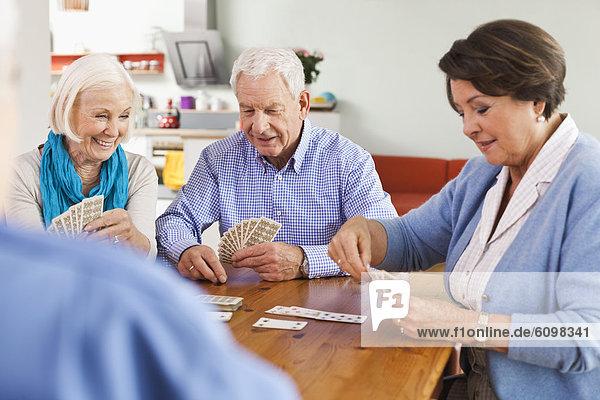 Ältere Männer und Frauen beim Kartenspielen  lächelnd